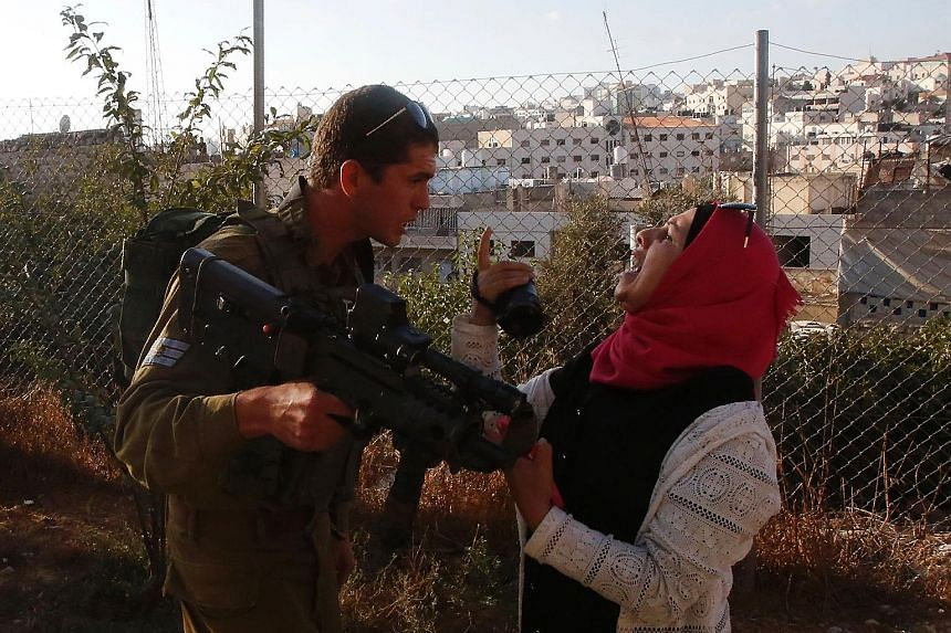 An Israeli soldier scuffling with a Palestinian woman, who was trying to film the scene of a stabbing attack by a Palestinian teenager on an Israeli soldier in Hebron, West Bank, on Friday. The 15-year-old attacker was shot to death, while the soldie