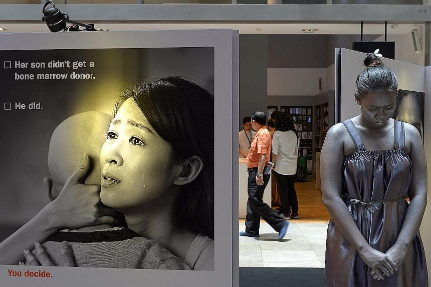 """Above: Visitors can sign up to be donors at an exhibition chronicling the stories of patients and their donors at 313@Somerset that closes today, or visit BMDP's website at bmdp.org. Left: Fifty """"living statues"""" went on display in Orchard Road to mar"""