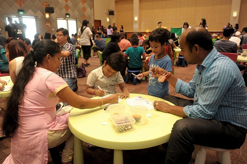 Mr Adimoolam Arasakumar and his wife Jayashankar Pabitha designing chef hats with their two children at the launch of the Play programme on Sept 18, 2016.