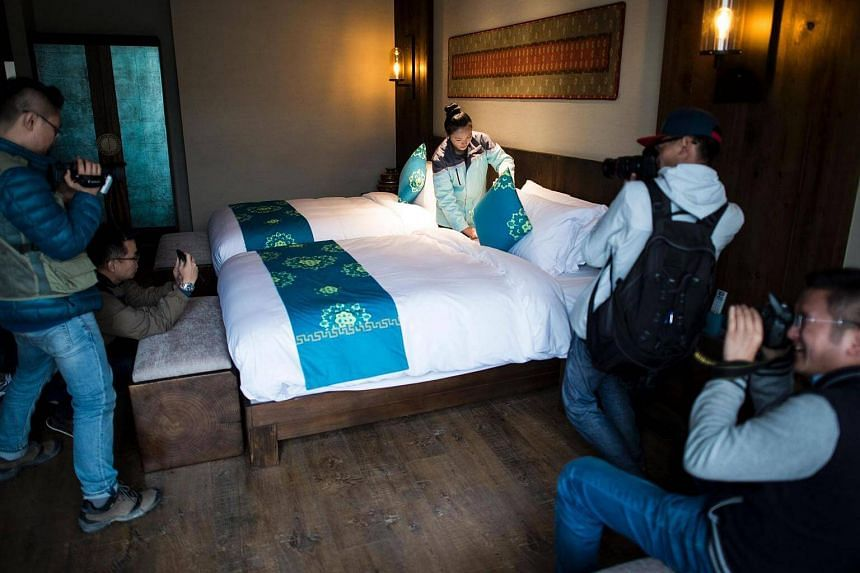 This picture taken on Sept 13, 2016 shows journalists and government photographers taking pictures of a worker cleaning a bed in a room of the Artel hotel in Lulang, part of China's Tibet Autonomous Region.