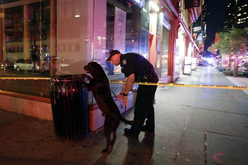 A New York City Police emergency services officer and his dog check a garbage can close to the scene of the explosion on 23rd Street between 6th and 7th Avenue in the borough of Manhattan in New York, USA, on Sept 17, 2016.