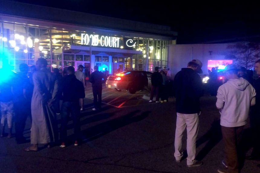 People stand outside the scene of the stabbing at the Crossroads Centre mall in St. Cloud, Minnesota in the US.