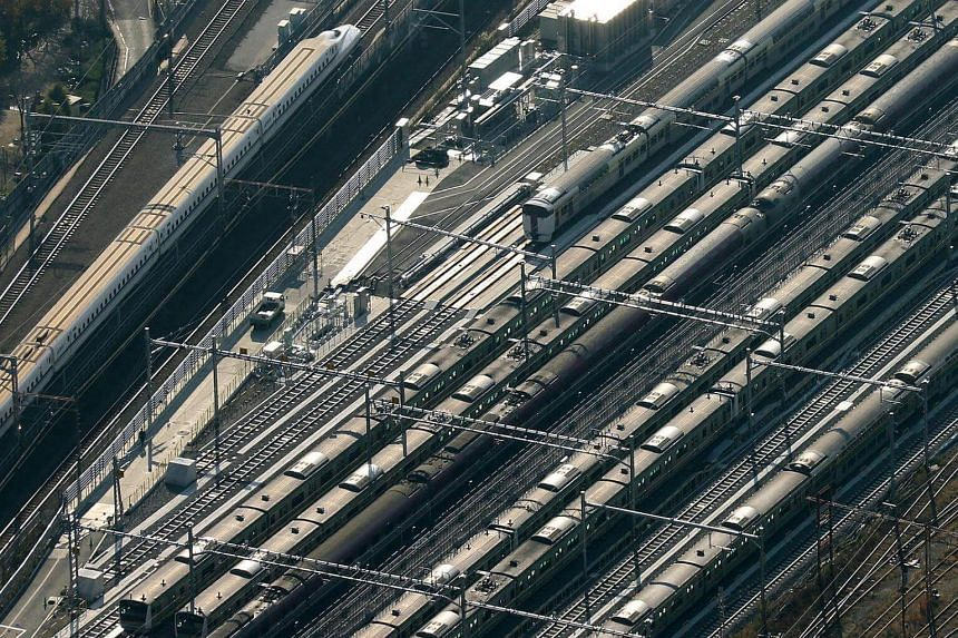 A Central Japan Railway Shinkansen bullet train (left) travels near East Japan Railway trains in this aerial photograph taken in Tokyo, Japan, on Dec 2, 2013.