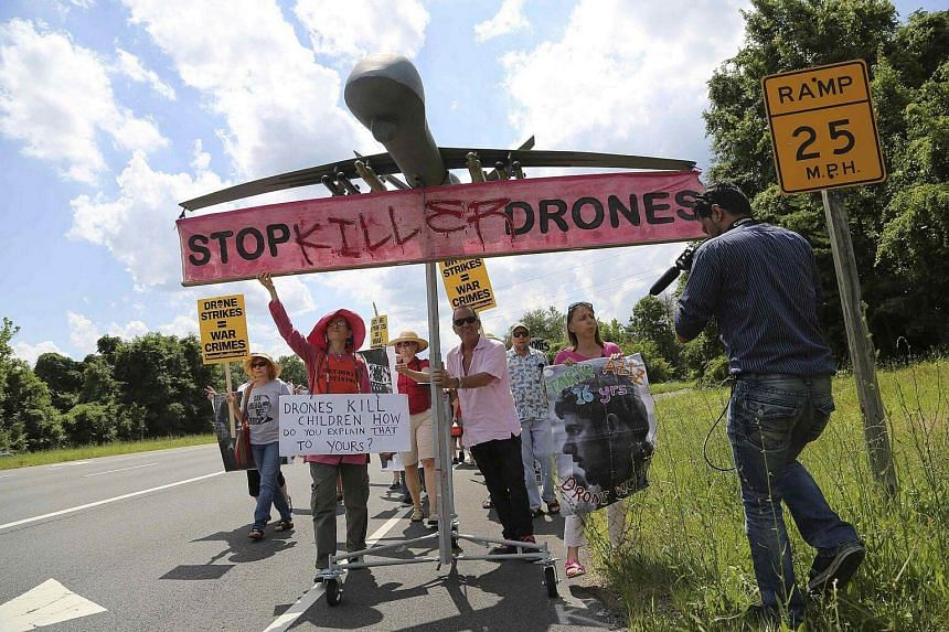 Protesters against drone strikes walk along the highway with a model of a drone as they gather outside CIA headquarters in Langley Virginia on June 29, 2013.