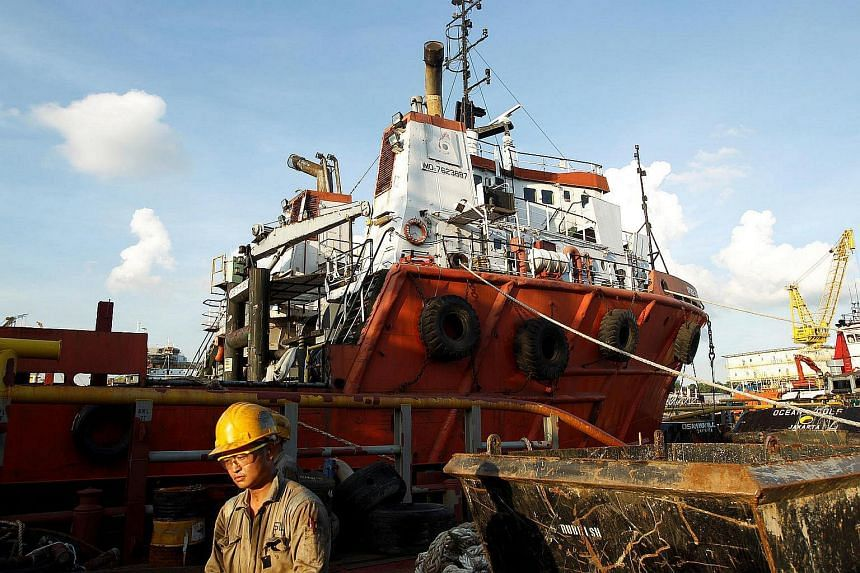 A worker passes a Swiber vessel at their shipyard in Singapore on July 10, 2013.