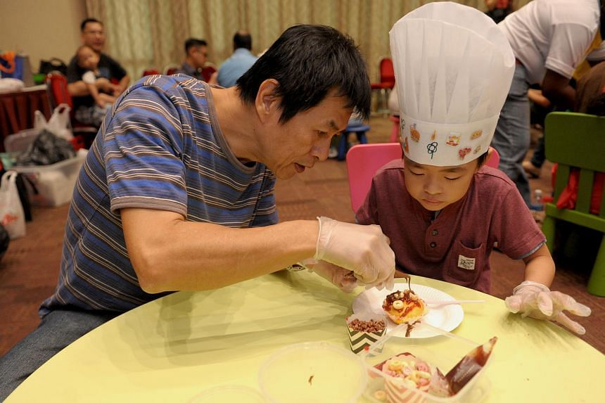 Mr Tan Yong Keng helping his son design a cupcake at launch of the Play programme on Sept 18, 2016.