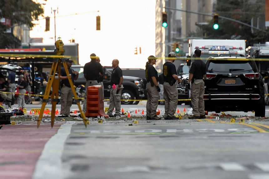 Evidence markers on the street surround Federal Bureau of Investigation officials near the site of an explosion in the Chelsea neighborhood of Manhattan, New York on Sept 18, 2016.