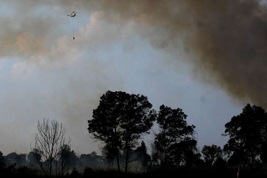 A helicopter from Indonesia's National Disaster Mitigation Agency conducts water-bombing operations to put out forest fires in southern Sumatra on Aug 3, 2016.