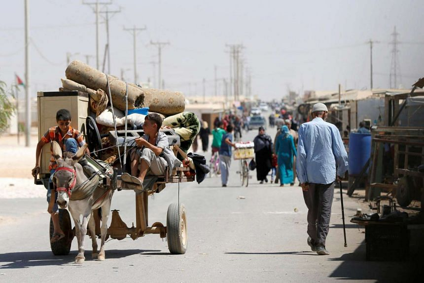 Syrian refugee children ride on a donkey-drawn cart in the Jordanian city of Mafraq. A summit to address the biggest refugee crisis since World War II opens at the United Nations on Monday (Sept 19).