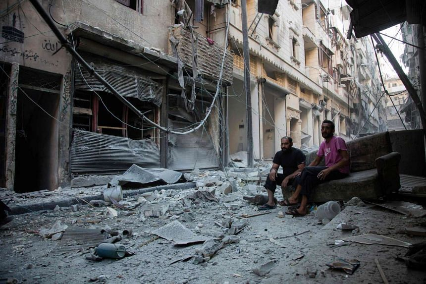 Syrians sit amid the destruction caused by an airstrike on the regime-controlled neighbourhood of Karm al-Jabal on Sept 18, 2016.