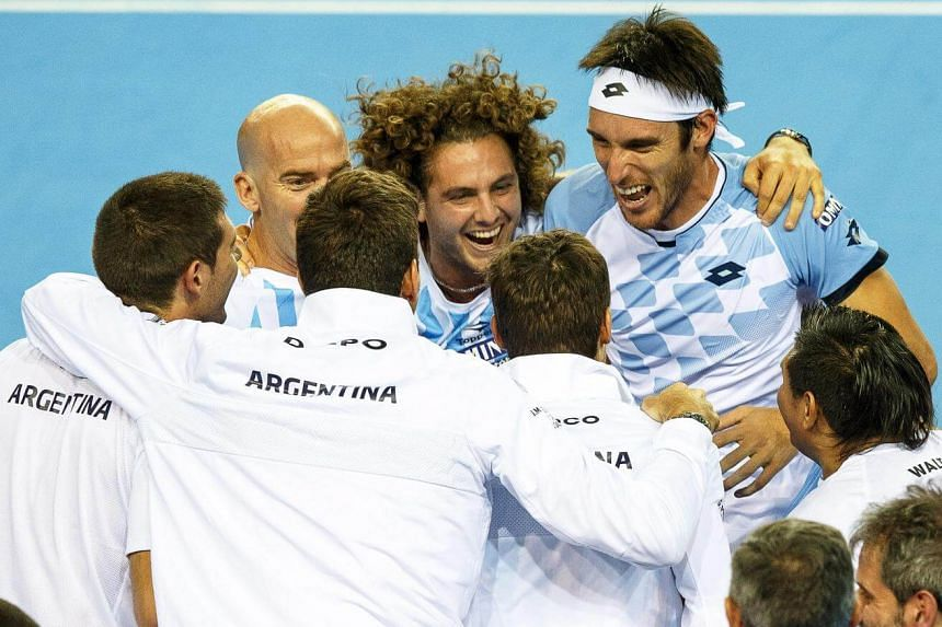 Leonardo Mayer (back right) of Argentina celebrates with his team members after defeating Daniel Evans of Britain during the Tennis Davis Cup semi-final tie between Britain and Argentina in Glasgow, Scotland, on Sept 18, 2016.