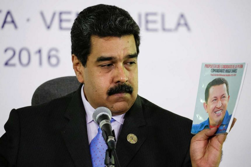 Venezuelan President Nicolas Maduro holds a book with a photo of late former president Hugo Chavez as he talks to the media during a news conference after the 17th Non-Aligned Summit in Porlamar, Venezuela on Sept 18, 2016.