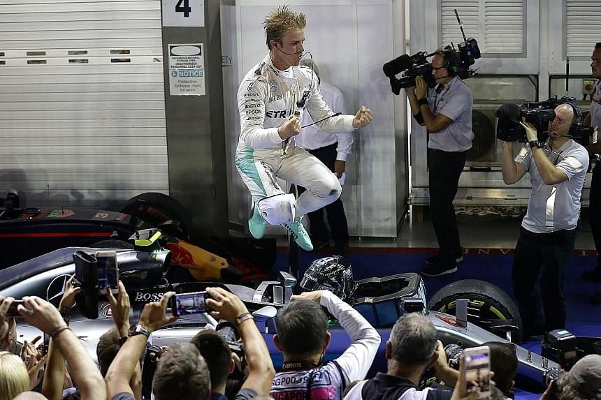 Rosberg celebrating after winning the Singapore Grand Prix at the Marina Bay Street Circuit last night. The German now tops the drivers' standings, eight points clear of his team-mate and title rival Lewis Hamilton, with six races left in the Formula