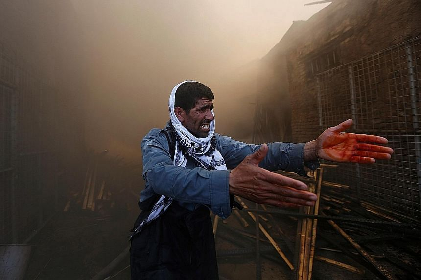 A police officer trying to communicate with firefighters (not in picture) battling a blaze that broke out at a construction wood market yesterday in Kabul, Afghanistan. Witnesses blamed the fire on carelessness, but the cause was as yet not known. Th