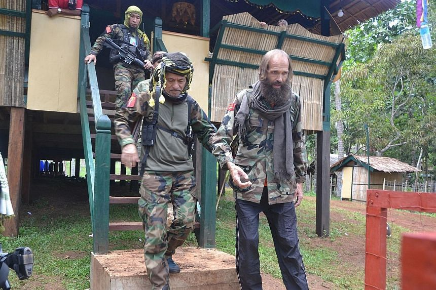 Rebel leader Nur Misuari (at left), whose group assisted in the hostage release, escorting Mr Sekkingstad in the town of Indanan on Jolo island yesterday. The Norwegian had been abducted by Abu Sayyaf militants in September last year.