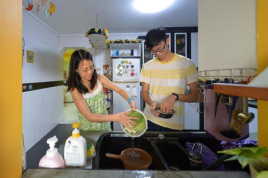 Student Timothy Chan, 16, and his mother Jackie, 46, washing vegetables and rice in their Tampines home. Over the years, there has been some progress in reducing water usage in Singapore homes.
