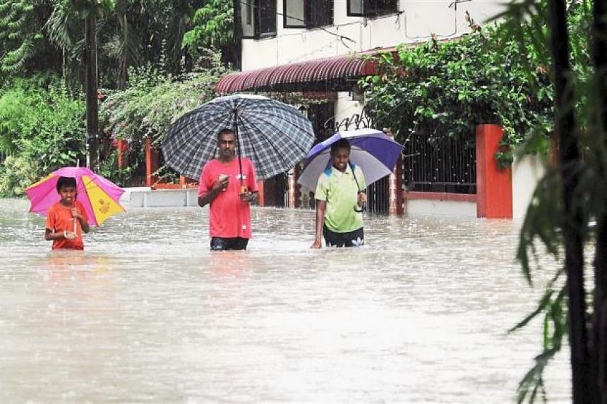 Residents of Kampung Lama, George Town walking through floodwater to get home.
