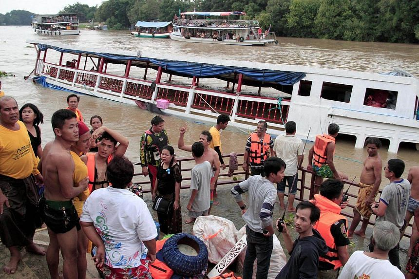 People stand near a boat which capsized on the Chao Phraya river while carrying Thai Muslims, in the ancient tourist city of Ayutthaya, Thailand, on Sept 18, 2016.