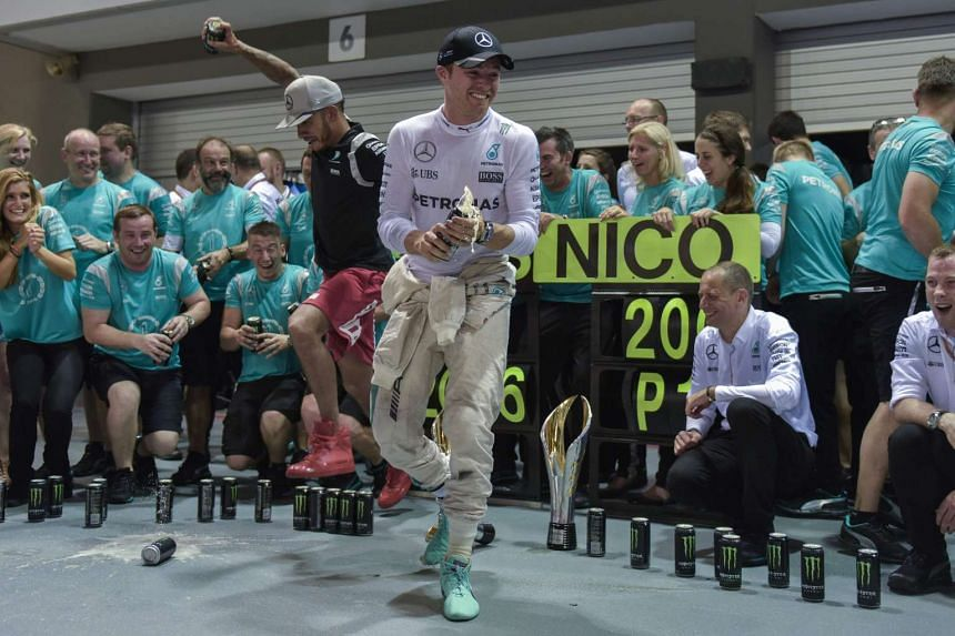 Mercedes AMG Petronas F1 Team's German driver Nico Rosberg (centre right) celebrates his victory with runner up Mercedes AMG Petronas F1 Team's British driver Lewis Hamilton (centre left) and their team members in Singapore on Sunday night (Sept 18).