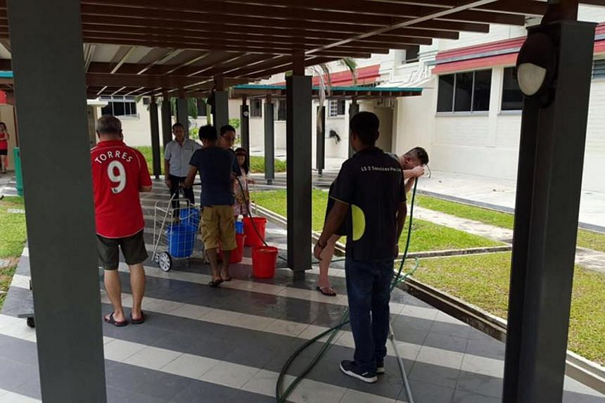 Residents of Tampines Block 508 collecting water from water points, after the water supply to the block was cut off while contractors investigated the source of a leak.