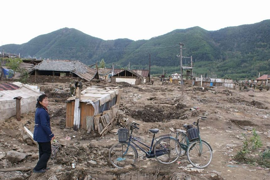 A North Korean woman stands amid the rubble of heavily damaged homes caused by floods in late August 2016 in the Sambong district of Musan in North Korea.