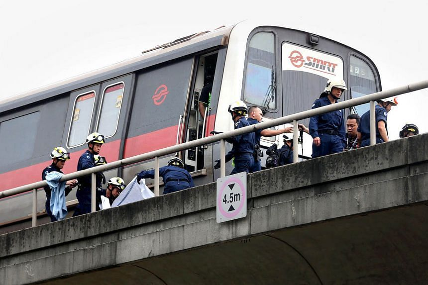 Paramedics from the Singapore Civil Defence Force retrieving one of the two bodies of SMRT maintenance staff who were killed in an accident along the train track near Pasir Ris MRT station on March 22.