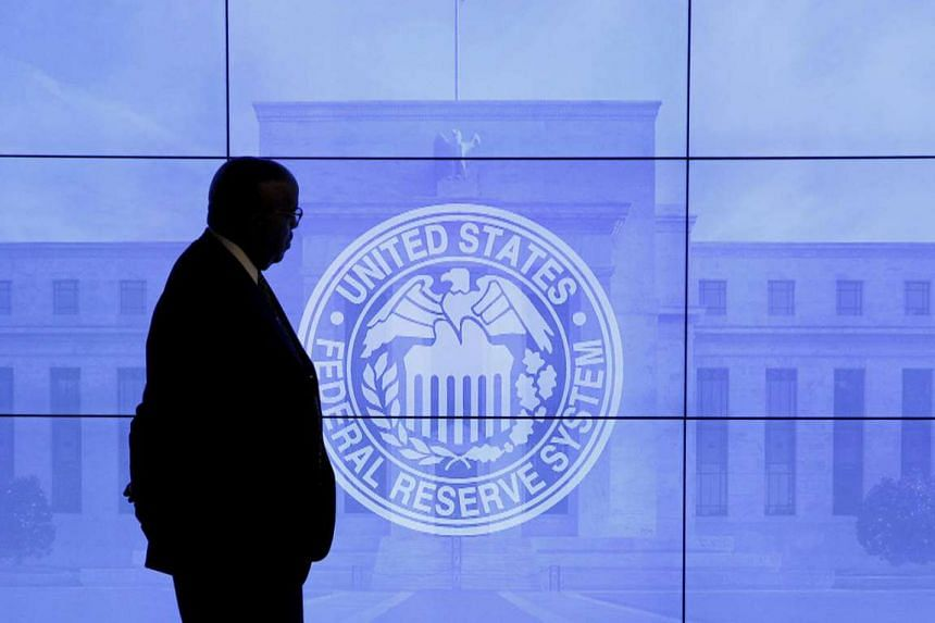 A guard walks in front of a Federal Reserve image on March 16, 2016.