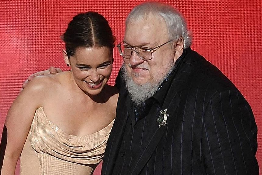 Actress Emilia Clarke and writer George R. R. Martin accepting the Emmy for Game Of Thrones.