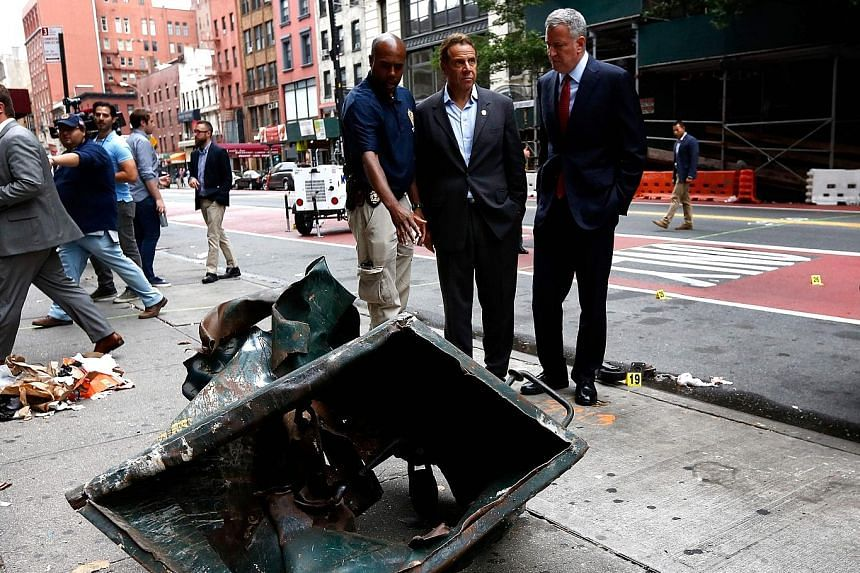 (From right) New York Mayor Bill de Blasio and Governor Andrew Cuomo on Sunday visiting New York City's Chelsea neighbourhood, where they were shown a dumpster mangled by the force of last Saturday's explosion.