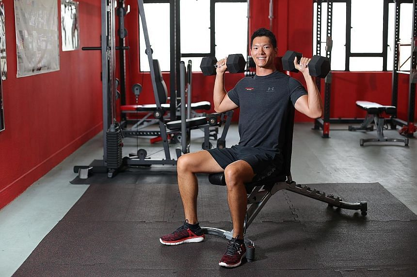 Mr Chung doing shoulder exercises with free weights.