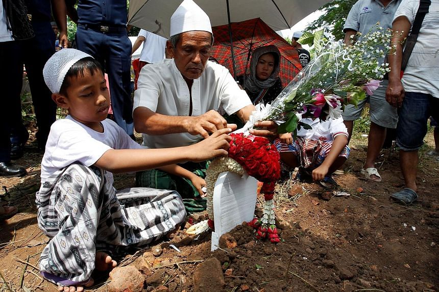 Relatives at a graveyard in the ancient tourist city of Ayutthaya attending the funeral of a victim of the overcrowded boat that sank in the Chao Phraya River on Sunday. At least 18 passengers died, while the boat's captain is in custody and faces a