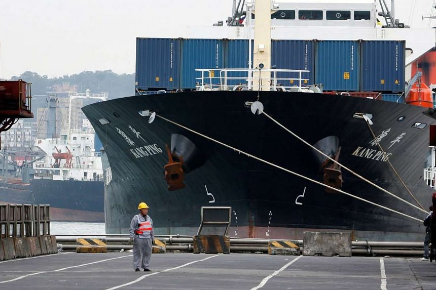 A man stands in front of a cargo ship at a port in the northern Taiwan city of Keelung.