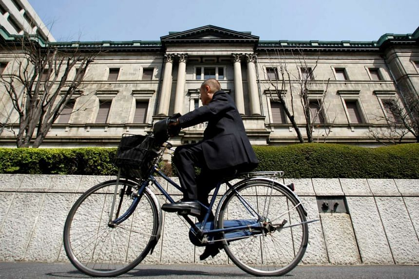 A man rides a bicycle past the Bank of Japan (BOJ) building in Tokyo.