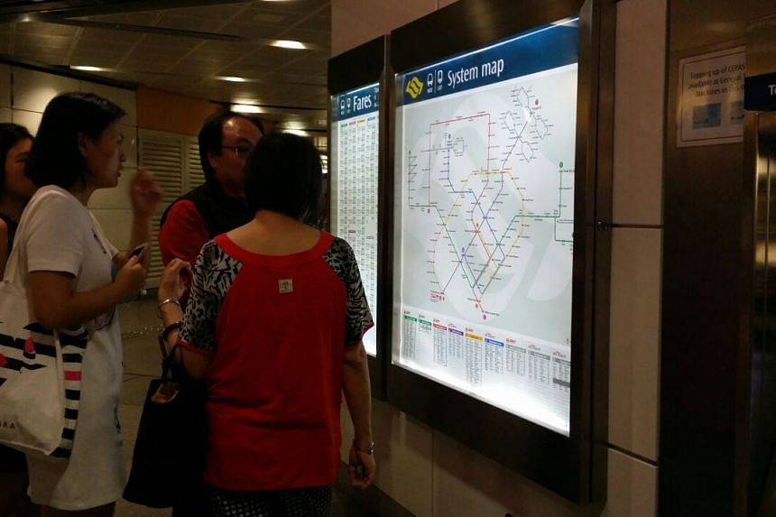 Commuters receive travel advice from a SMRT staff member.