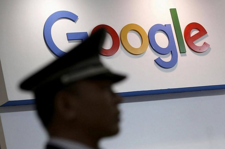 A security guard keeps watch as he walks past a logo of Alphabet Inc's Google.