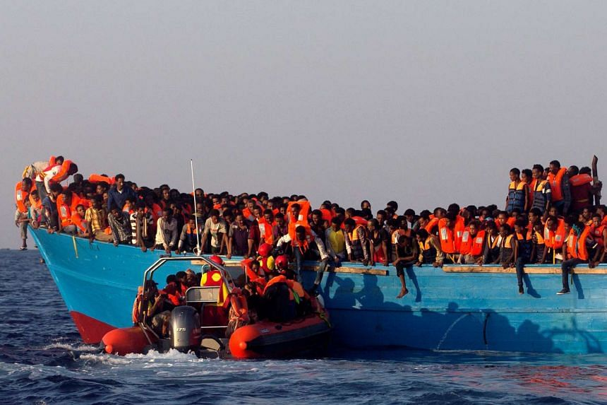 A Spanish rescue boat approaches an overcrowded wooden vessel with migrants from Eritrea, in the Mediterranean Sea, on Aug 29, 2016.