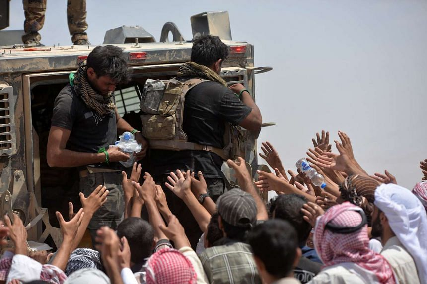 Iraqi security forces help civilians, who fled from Al-Shirqat because of ISIS violence, on the outskirts of Al-Shirqat, south of Mosul, in June.
