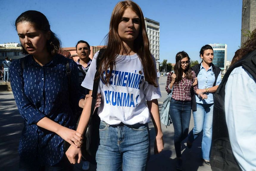 "Turkish police detain a student wearing a T-shirt reading ""Don't touch my teacher!"" in Diyarbakir on Monday (Sept 19) during a protest against the suspension of teachers."