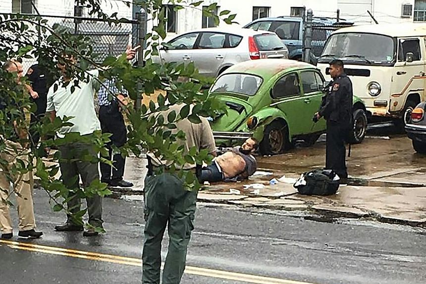Rahami lying wounded on the ground following a shoot-out with police yesterday in Linden, New Jersey. The police are investigating whether Rahami could have been influenced by international militant groups or the Afghan conflict.