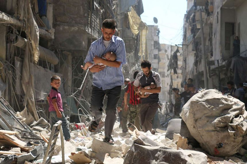 Syrian men carrying babies make their way through the rubble of destroyed buildings following a reported air strike on the rebel-held Salihin neighbourhood of the northern city of Aleppo, on September 11, 2016. Air strikes have killed dozens in rebel