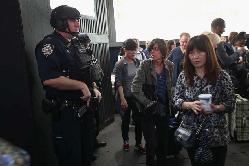 Commuters pass heavily armed New York City policemen at Penn Station on September 19, 2016 in New York City. Police and military presence was heavy following weekend bomb explosions in New York City and New Jersey. Meanwhile, some 200 world leaders a