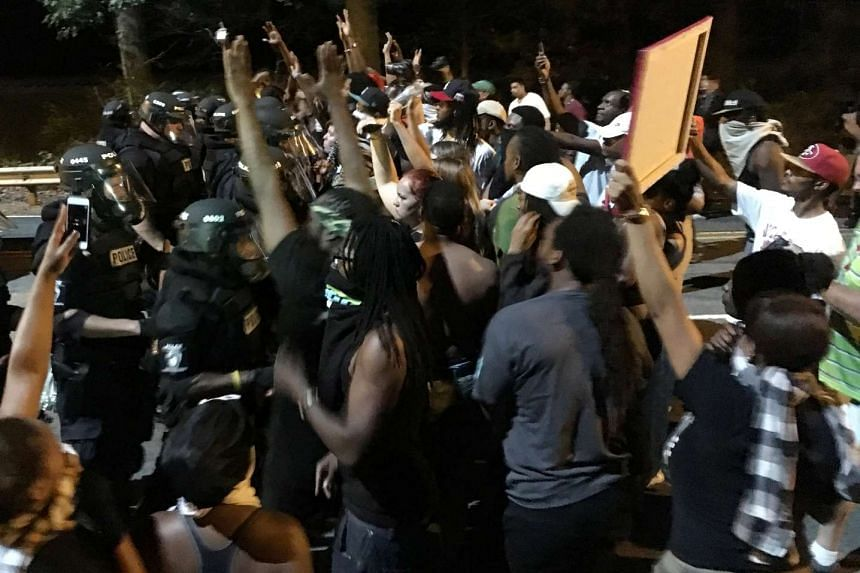 Protestors demonstrating in front of police officers in riot gear in Charlotte, North Carolina, on Sept 20, 2016.