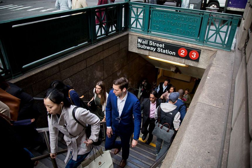 Commuters exit a Wall Street subway station near the New York Stock Exchange (NYSE) in New York.