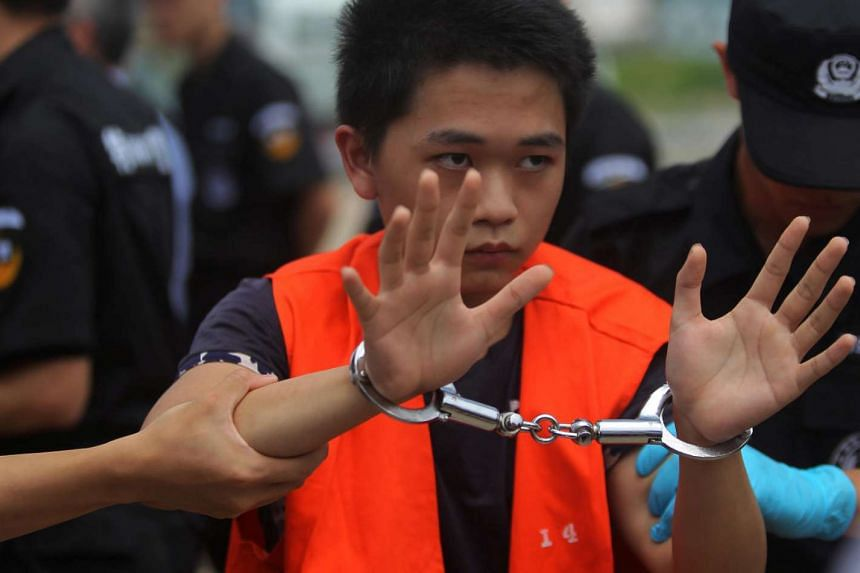 A suspect of telecom fraud is escorted by China police Swat team and a Cambodian police as they were deported to China.