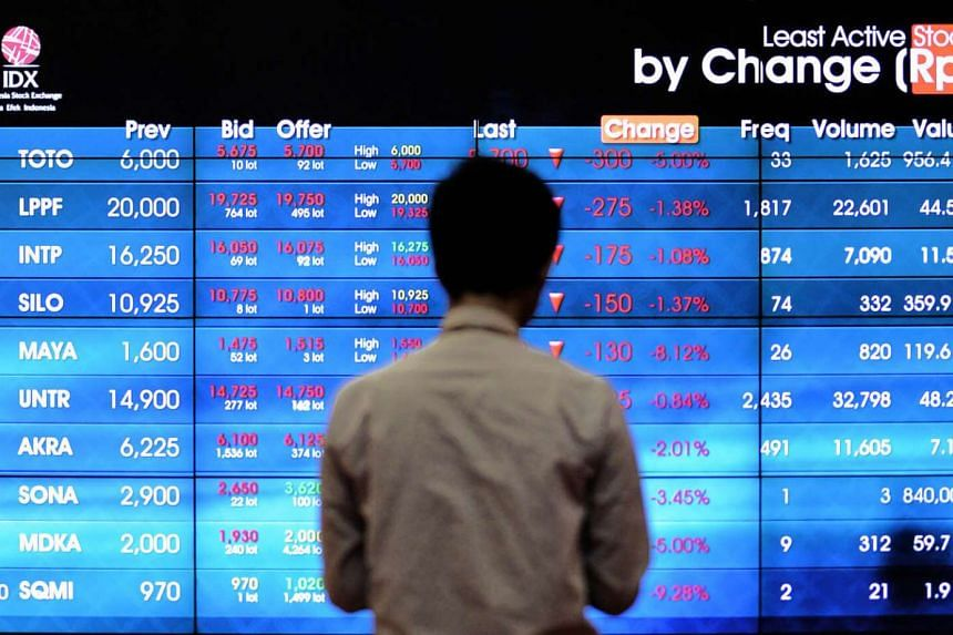 An Indonesian man looks at the stock exchange share prices board in Jakarta.