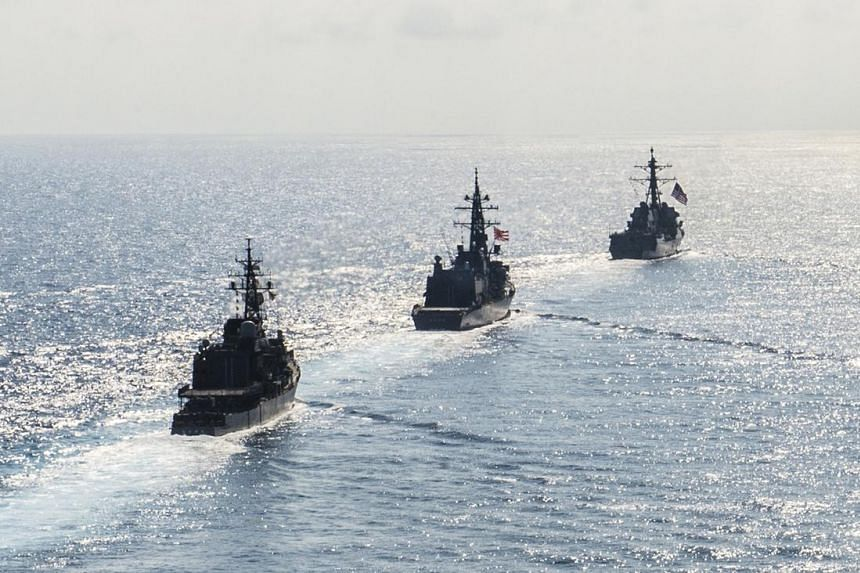Arleigh Burke-class guided-missile destroyer USS Mustin (DDG 89) transits in formation with Japan Maritime Self-Defense Force ships JS Kirisame (DD 104) and JS Asayuki (DD 132) during bilateral training in South China Sea.
