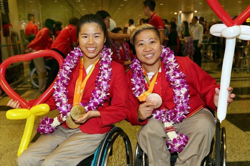 Para-swimmers Yip Pin Xiu and Theresa Goh pose with their medals after landing at Changi International Airport on Sept 21, 2016.
