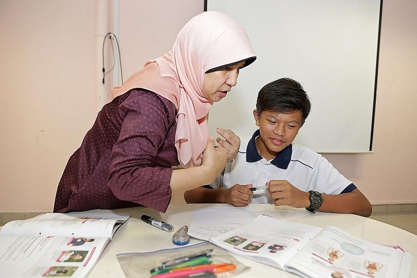 Amirul Afiq Rozlan, a Secondary 2 student at Balestier Hill Secondary who was diagnosed with hearing loss in 2005, at a science remedial class taught by Madam Nafisah Mohd Amin, 49. She communicates with the 15-year-old using sign language.