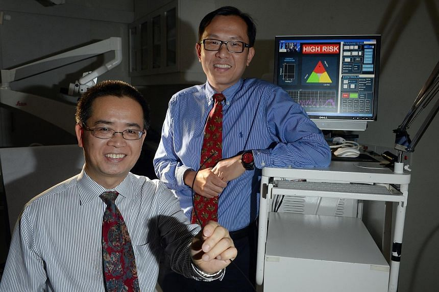 Dr Lim (left) and Prof Huang (far left) of NUS, with the Raman spectroscopy equipment they developed for detecting nose cancer early.