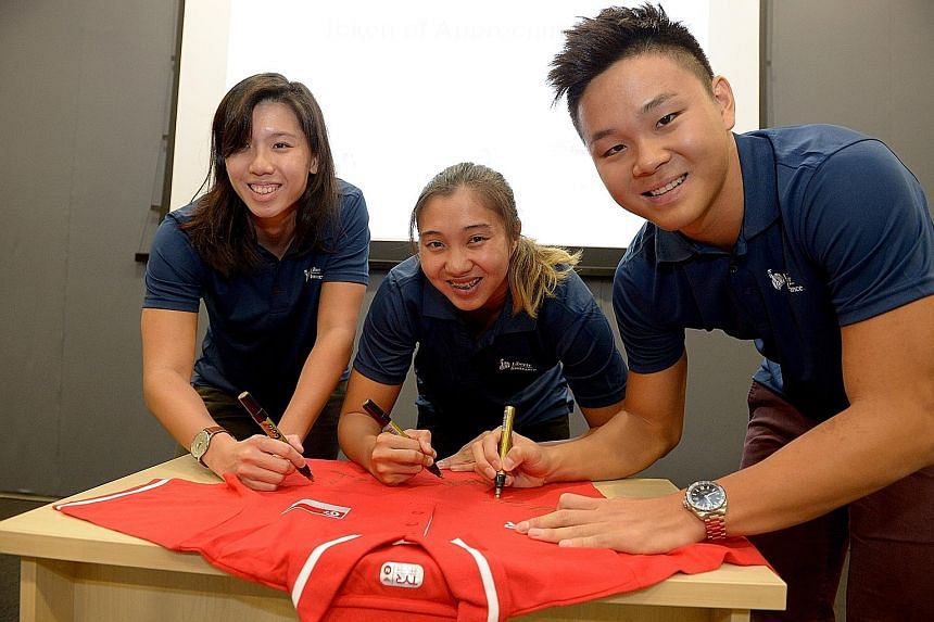 (From left) Singapore swimmers Amanda Lim, Marina Chan and Pang Sheng Jun signing a shirt, which was presented to Liberty Insurance CEO Chang Sucheng. The trio will compete at the swimming World Cup leg in Singapore.